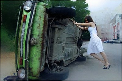 Woman in white dress pushing a car that rolled over